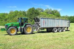 John Deere 7930 traktor med person som ger drickssemitraileren Fliegl Gigant ASW 393 Arkivfoton