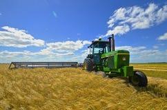 John Deere traktor och swather i vetefält Royaltyfria Foton