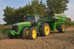 John Deere 8420 John Deere traktor som drar en kornvagn Arkivfoto