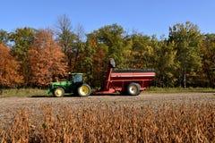 John Deere 8400 traktor som drar en sojabönavagn Arkivfoto