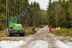 John- Deereerntemaschine, die im Wald, Winterzeit arbeitet stockfotografie