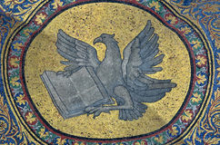 John the Evangelist. Golden mosaic of an eagle and book, representing the evangelist St John, who wrote one of the four gospels Stock Photography