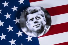 John F Kennedy and the USA Flag. LONDON, UK - APRIL 27TH 2018: A John F. Kennedy badge pictured over the USA Flag, on 27th April 2018. John F Kennedy was the royalty free stock images