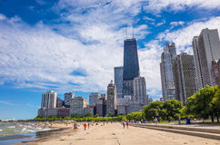 John Hancock building on Michigan Av in Chicago. CHICAGO-August 18: John Hancock building on Michigan Av in Chicago,IL with people on the beach August 18,2013 Royalty Free Stock Images