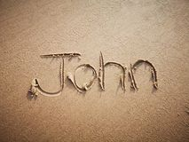 A John name written on the beach. An English John name written on the beach stock photography