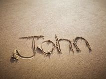 A John name written on the beach. An English John name written on the beach stock photo