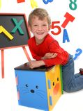 John Nicholas. Happy young boy in preschool on isolated white background with bright letters and numbers royalty free stock photos