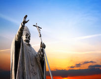 The direction of truth and life. The John Paul II statue on the sunset background Royalty Free Stock Images