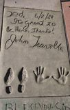 John Travolta's imprint by the Chinese Theatre. John Travolta's hand and footprints, and handwritten message, on the Hollywood walk of fame on Hollywood royalty free stock image