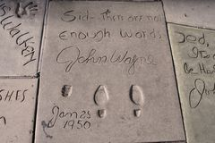 John Wayne's imprint by the Chinese Theatre. John Wayne's hand and footprints, and handwritten message, on the Hollywood walk of fame on Hollywood Boulevard in stock image