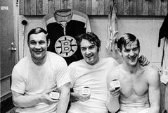 Johnny Bucyk, Eddie Johnston and Bobby Orr. Boston Bruins stars Johnny Bucyk, Eddie Johnston and Bobby Orr hold up pucks commemorating accomplishments after a Royalty Free Stock Image