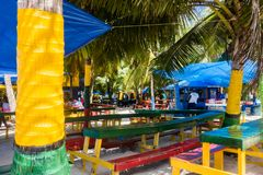 JOHNNY CAY, COLOMBIA - OCTOBER 21, 2017: Close up of some typical wooden tables with the color of colombian flag. Outdoor view of restaurant, under some palms Royalty Free Stock Photos