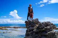 JOHNNY CAY, COLOMBIA - OCTOBER 21, 2017: Unidentified blonde woman enjoying the beautiful sunny day over a rock in the. Coast of Johnny Cay island Royalty Free Stock Photography