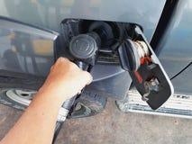 JOHOR MALAYSIA - AUGUSTI 9, 2017: En hand som rymmer dysan för pump för diesel- bränsle under att fylla på bränsle in i bilbehåll Arkivbilder