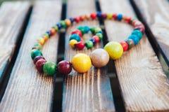 Joia colorida feito a mão Grânulos coloridos e bracelete de madeira Fundo de madeira foto de stock royalty free
