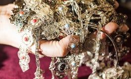 Joia de prata com as pedras preciosas vermelhas e azuis em uma mão Foto de Stock
