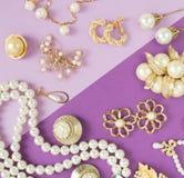 Joia do ` s da mulher Fundo da joia do vintage Broches goldtone e das pérolas, braceletes, colares e brincos bonitos no purpl fotos de stock royalty free