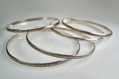 Joia feminino - prata, braceletes velhos em um fundo branco fotos de stock royalty free