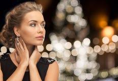 Joia vestindo da mulher sobre luzes de Natal imagens de stock royalty free