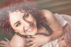 Joie de jeune femme de sourire avec les cheveux rouges bouclés Photographie stock