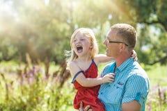 Joie heureuse de famille de papa et de fille en nature Photos stock