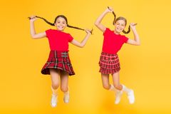 Join celebration. Cheerful friends schoolgirls jumping yellow background. Celebrate holiday. Scottish holiday. Kids girl. Wear checkered dresses. National royalty free stock images