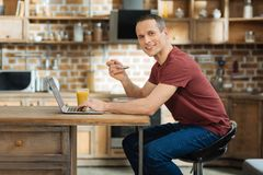 Cheerful male person looking straight at camera. Join me. Handsome brunette keeping smile on his face and turning head while eating porridge Royalty Free Stock Photography