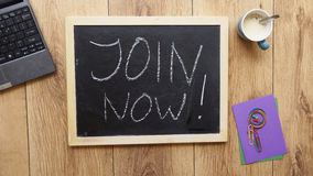 Join now written. On a chalkboard at the office stock photo
