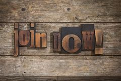 Join Now written with letterpress type. Join now, phrase set with vintage letterpress printing blocks on rustic wooden background Stock Images