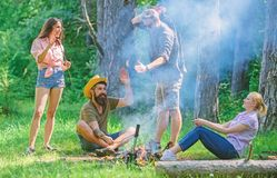 Join summer picnic. Company having fun while roasting sausages on sticks. Friends meeting near bonfire to hang out and stock images