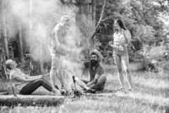 Join summer picnic. Company having fun while roasting sausages on sticks. Gathering for great picnic. Friends meeting royalty free stock images