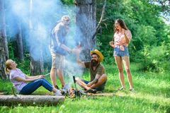 Join summer picnic. Company having fun while roasting sausages on sticks. Gathering for great picnic. Friends meeting Stock Image