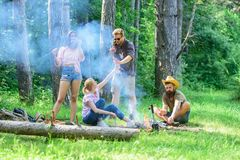 Join summer picnic. Gathering for great picnic. Company having fun while roasting sausages on sticks. Friends meeting Royalty Free Stock Images