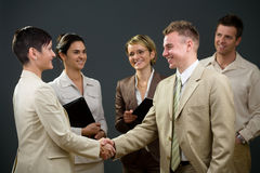 Join us. Businessman and businesswoman shaking hands in front of smiling colleagues Stock Photos