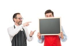 Join us. Hiring restaurant staff. Hipster bartender show blackboard copy space. Men bearded informing. Men bearded. Bartender in apron hold blank chalkboard stock photos
