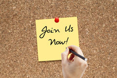 Join us now. Woman hand writing Join us now note pinned on cork noticeboard Stock Photo