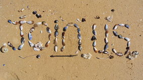 Join us. These two words Join us was created using seashells and arranging them on wet beach sand. There is text, seashells, wet beach sand and some seaweed in royalty free stock image