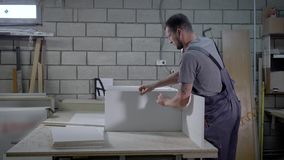 Joiner is assembling a wardrobe, fixing processed particle boards using hand drill, twisting screws. Working process on factory stock video footage