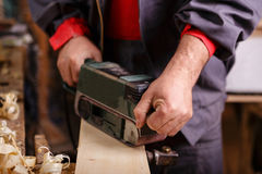 Joiner with a belt sander on a wooden board Stock Photo