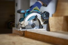The joiner cuts a wooden board with an electric saw stock photography