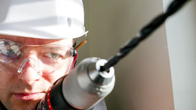 Joiner drilling in the wall Stock Image