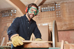 Joiner with grinding machine. At carpentry workshop Stock Image