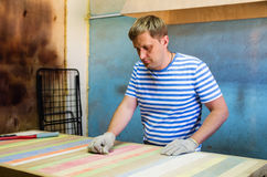 Joiner handles wooden surface countertops emery cloth. The picture was taken in a furniture shop in the city of Orenburg, Russia Stock Photo