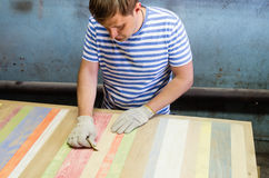 Joiner handles wooden surface countertops sandpaper. Furniture shop. The picture was taken in a furniture shop in the city of Orenburg, Russia Stock Images