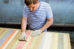 Joiner handles wooden surface countertops sandpaper. Furniture shop Stock Images