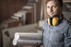 Joiner holding projects. Portrait of young accurate joiner with muffs holding projects Stock Images