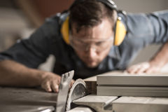 Joiner sawing wood. Portrait of accurate joiner sawing wood using electric saw Royalty Free Stock Photos