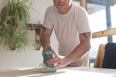 Joiner using a sander on a table surface Stock Photography