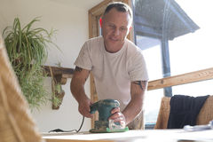 Joiner using a sander on a table surface Royalty Free Stock Photo