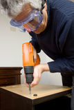 Joiner at work. With some furniture at home Stock Images
